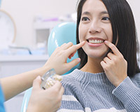 woman and dentist both pointing to smile