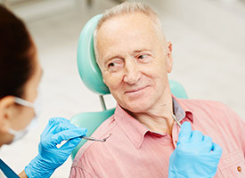 man in peach shirt looking at dentist