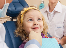 little girl in blue exam chair
