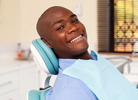 man smiling in green exam chair