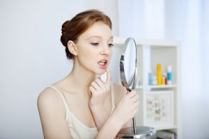 woman checking mouth in mirror whether she needs dentist in Canton